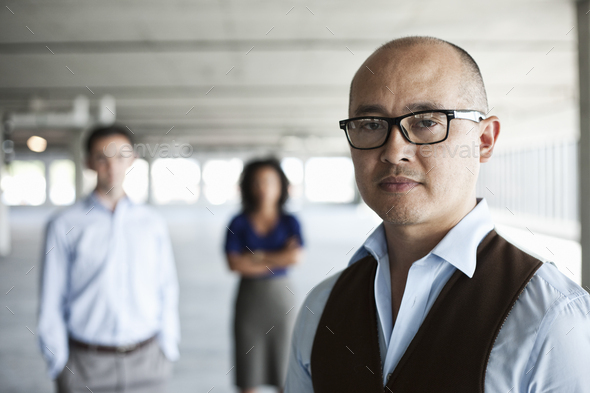 Portrait of a mixed race team of business people in a new empty office space. - Stock Photo - Images