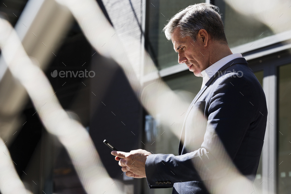 A man standing outside under a tree checking his phone, looking down at the screen. Communication on - Stock Photo - Images