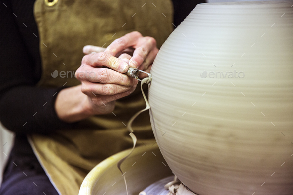 Close up of potter wearing apron working on spherical clay vase on pottery wheel. - Stock Photo - Images