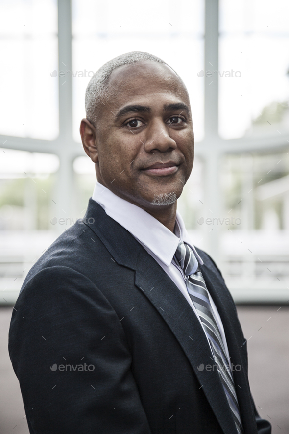 View of a black business man in a dress shirt, tie and suit coat - Stock Photo - Images