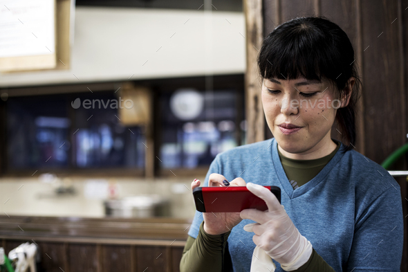 Smiling Japanese woman wearing one glove holding a red smart phone and checking messages. - Stock Photo - Images