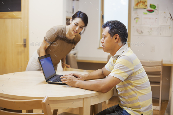 Family home. A man seated using a laptop. - Stock Photo - Images