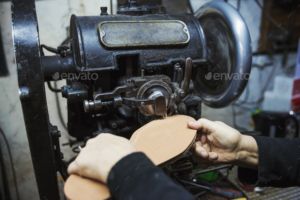 Close up of worker in a shoemaker's workshop, using a machine to sew a leather sole. - Stock Photo - Images
