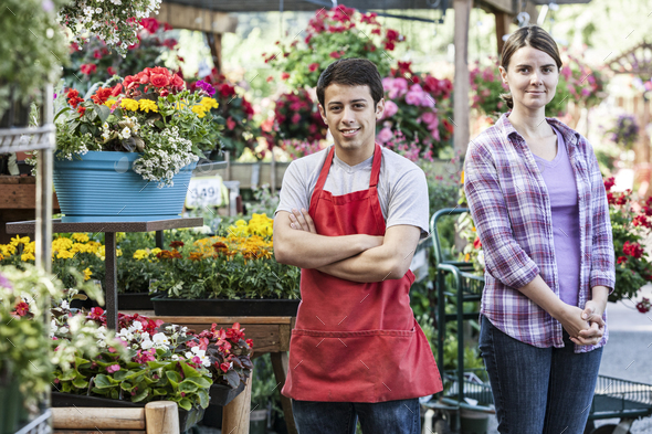 Caucasian man and woman employees of a garden center nursery. - Stock Photo - Images