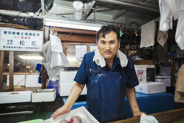 A traditional fresh fish market in Tokyo. A man in a blue apron standing behind the counter of his - Stock Photo - Images