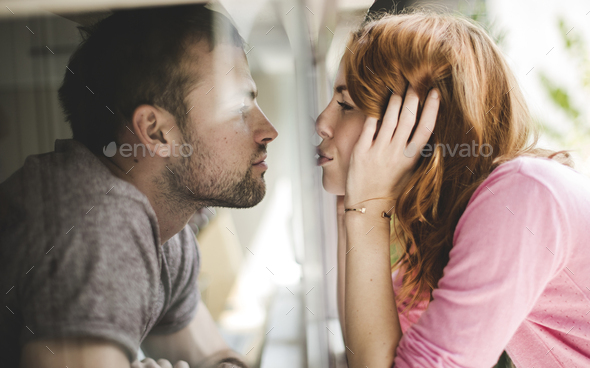A couple kissing through a pane of glass of a window. - Stock Photo - Images
