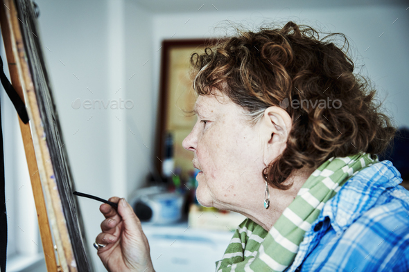 An artist working at her easel, using charcoal on paper to create an artwork. - Stock Photo - Images
