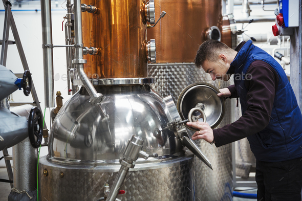 Man looking into a metal tank in a distillery. - Stock Photo - Images
