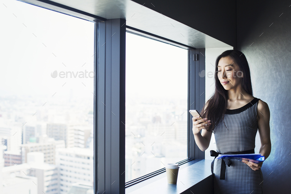 A business woman by a window with a view over the city, using her smart phone. - Stock Photo - Images
