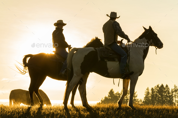 Two cowboys riding on horseback in a Prairie landscape at sunset. - Stock Photo - Images