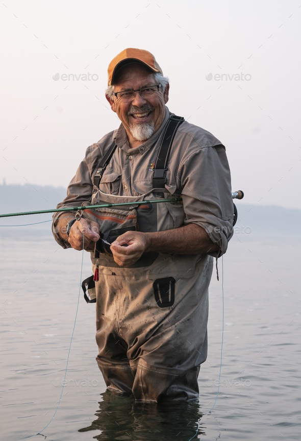 Caucasian senior male tying a fly on his fly fishing line while fishing for salmon and searun - Stock Photo - Images