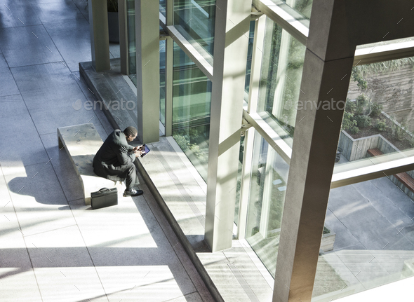 Black business man on a notebook computer sitting in a waiting area of a large open lobby. - Stock Photo - Images