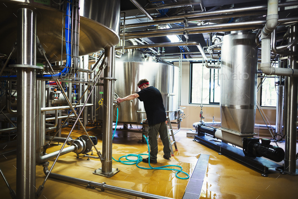 Man working in a brewery adjusting and checking the machinery which transfers the brewed beer around - Stock Photo - Images