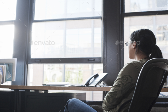 Asian woman working at her desk in a creative office. - Stock Photo - Images