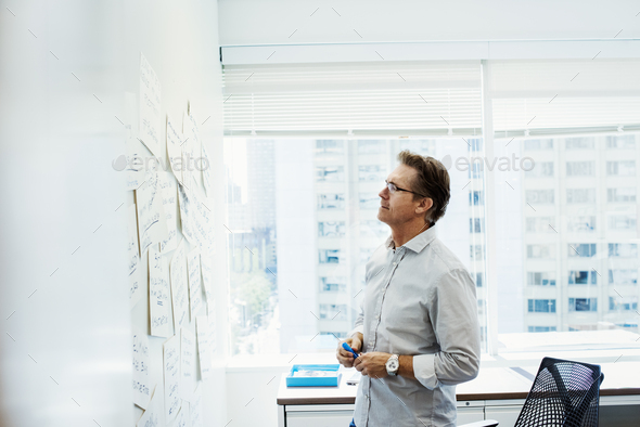 A man standing in an office looking at pieces of paper pinned on a whiteboard. - Stock Photo - Images