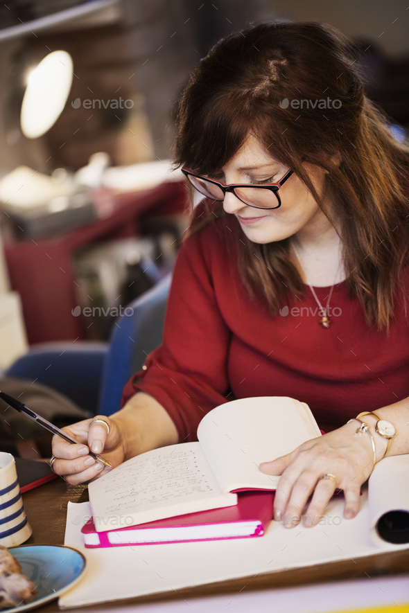 A woman seated at a table making notes, writing in a notebook. - Stock Photo - Images