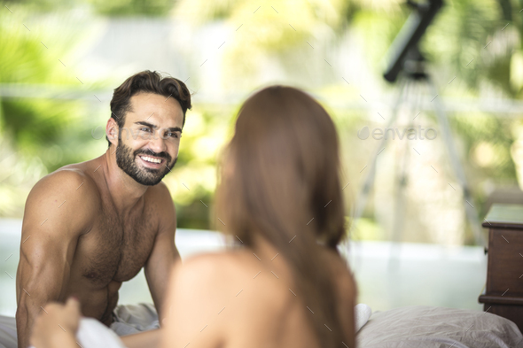 A man and woman sitting on a bed talking. - Stock Photo - Images