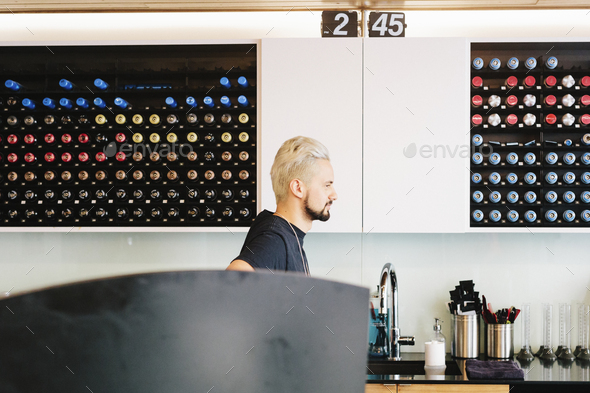 A man in profile standing by a sink in a hair salon. - Stock Photo - Images