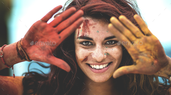 Young woman holding paint covered hands up to her face, one red and one yellow, smiling, Framing her - Stock Photo - Images