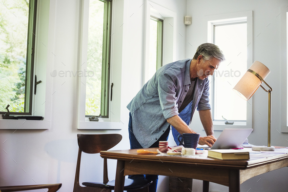 A man at home using a laptop on a desk. - Stock Photo - Images
