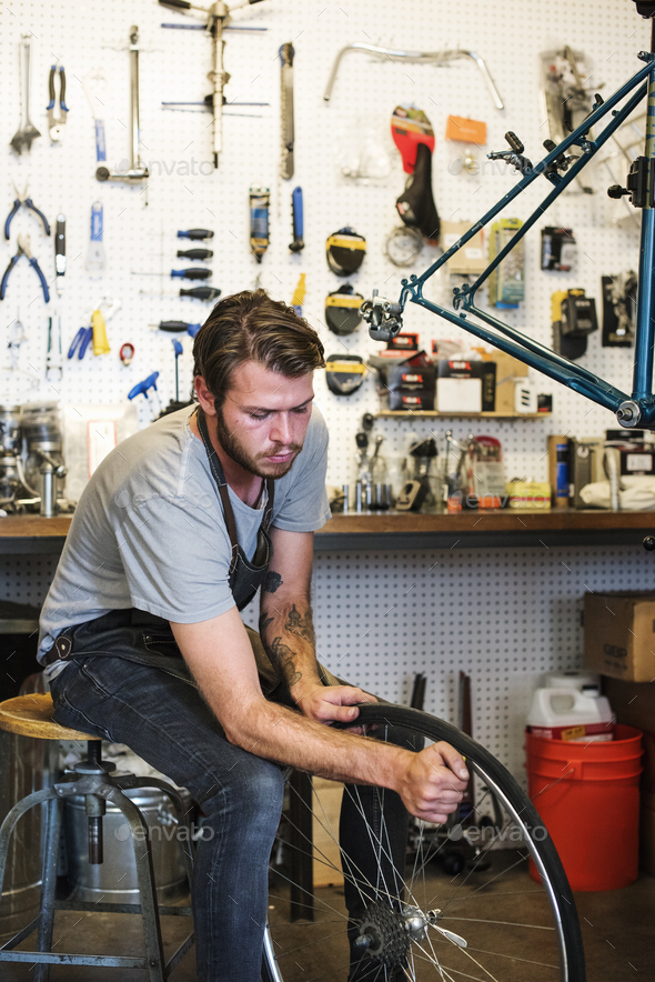A man working in a bicycle repair shop. - Stock Photo - Images