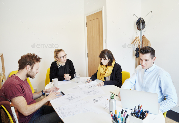Four people at a business meeting around a table spread with papers, one man using a tablet and one - Stock Photo - Images
