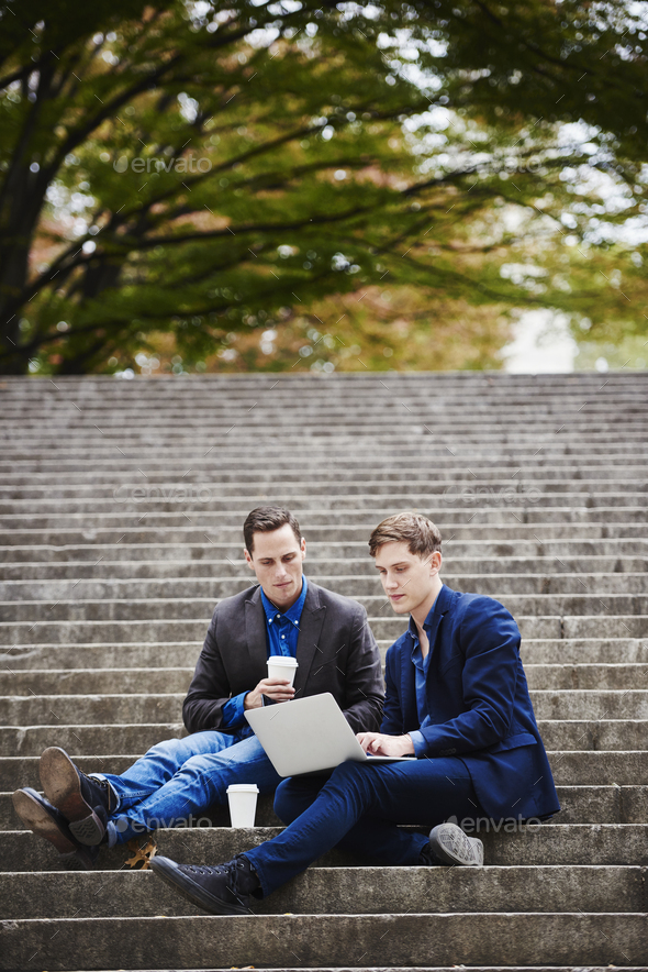 Two young men sitting on a flight of steps outdoors, looking at a laptop together. - Stock Photo - Images