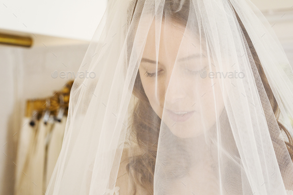 Head and shoulders of a woman trying on a net bridal veil in a specialist wedding dress shop. - Stock Photo - Images