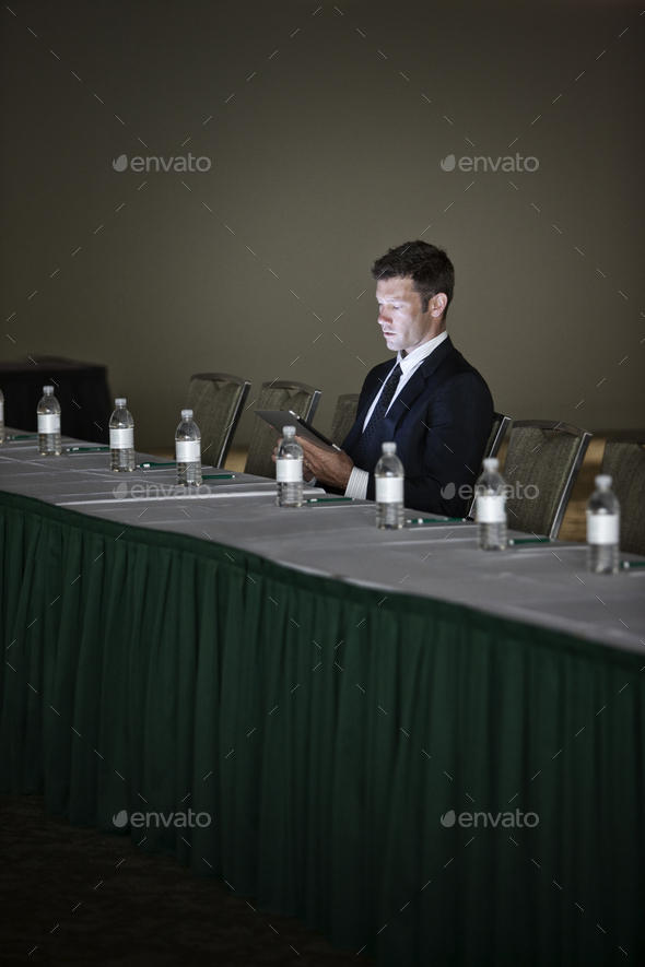 Caucasian businessman sitting alone and using a notebook computer at a convention center table. - Stock Photo - Images