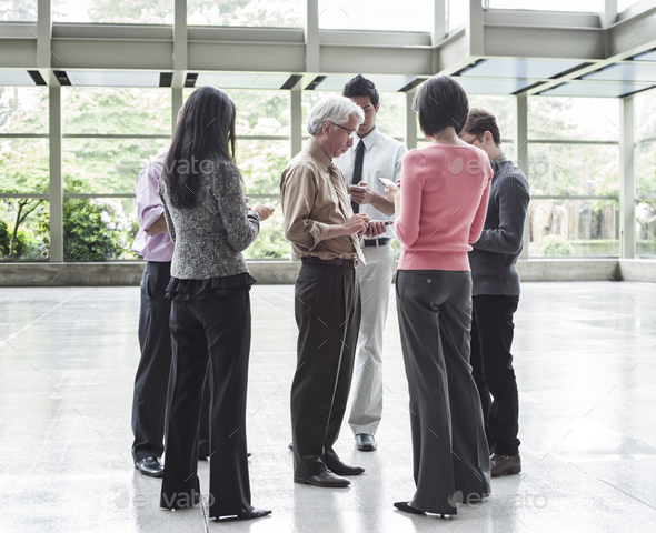 A mixed race group of male and female business people standing in the lobby area of a convention - Stock Photo - Images
