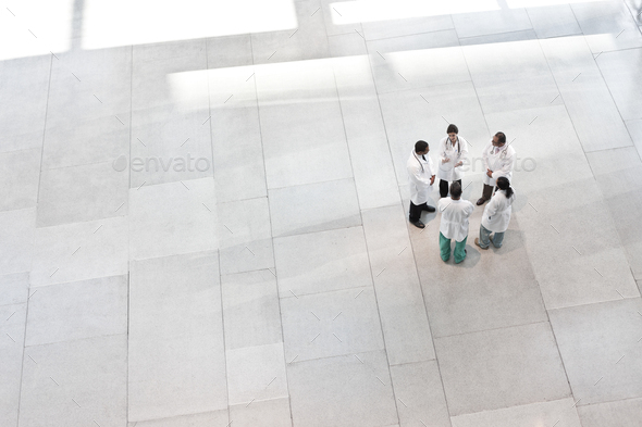 Mixed race group of doctors meeting in lobby of large hospital - Stock Photo - Images