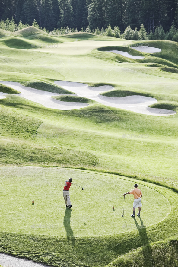 View from above of two golfer teeing off on a golf course. - Stock Photo - Images