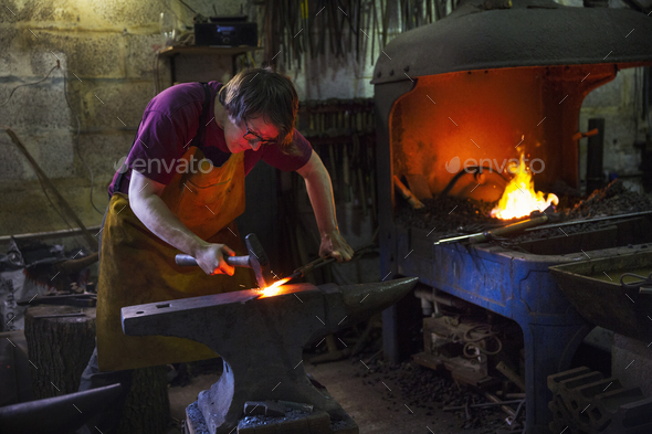 A blacksmith striking red hot metal on an anvil inside a workshop. - Stock Photo - Images
