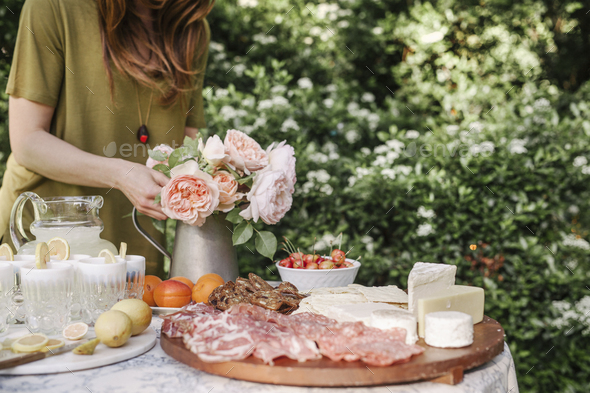 Woman standing at a table in a garden, a vase of pink roses, drinks, a bowl of cherries and a wooden - Stock Photo - Images