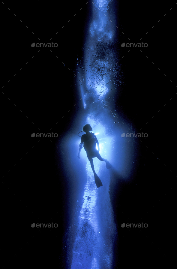 Diver silhouetted against the entrance to an underwater cave, Solomon Islands. - Stock Photo - Images
