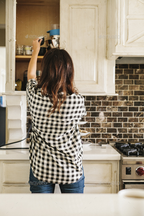 Rear view of  woman with long brown hair, wearing a chequered shirt, standing in a kitchen. - Stock Photo - Images