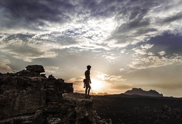 Mountaineer standing on top of a rock formation in a mountainous landscape. - Stock Photo - Images