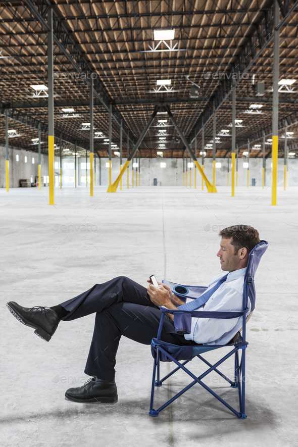 Caucasian man sitting in the middle of a new empty warehouse and using cell phone. - Stock Photo - Images