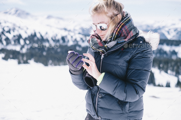 A woman on the ski slopes looking at her smart phone. - Stock Photo - Images