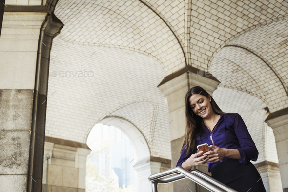 A woman with long hair standing under an arched ceiling checking her mobile phone. - Stock Photo - Images