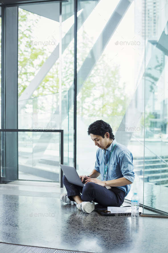 Businessman wearing blue shirt sitting on floor indoors, leaning against glass wall, working on - Stock Photo - Images