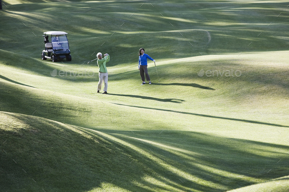 A young senior couple playing golf in the fairway of a golf course. - Stock Photo - Images