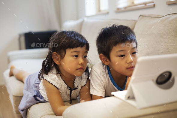 Family home. A boyand a girl lying on a sofa watching a digital tablet. - Stock Photo - Images