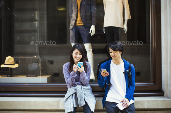 Young Japanese man and woman enjoying a day out in London, using a smartphone. - Stock Photo - Images