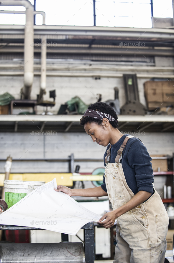 Black woman factory worker going over project plans in a sheet metal factory. - Stock Photo - Images