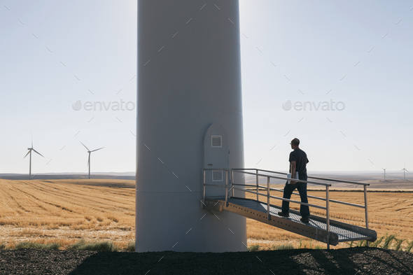 A wind farm technician standing and using a laptop at the base of a turbine on a wind farm in open - Stock Photo - Images