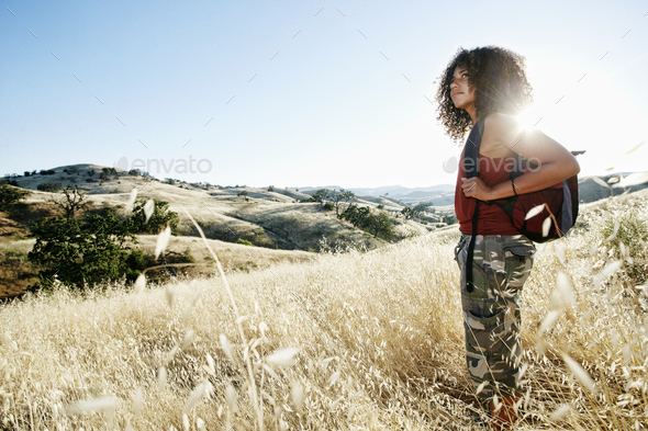 Young woman with curly brown hair hiking in urban park. - Stock Photo - Images