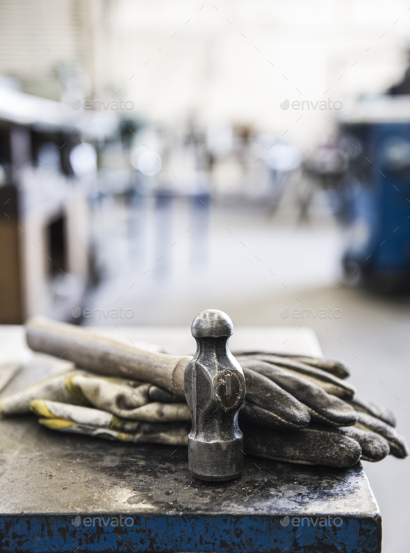 Closeup still life of gloves and a heavy duty hammer in a sheet metal factory. - Stock Photo - Images