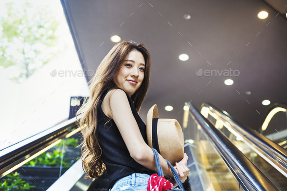 Smiling young woman with long brown hair on an escalator. - Stock Photo - Images