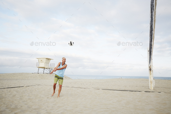Mature man standing on a beach, playing beach volleyball. - Stock Photo - Images